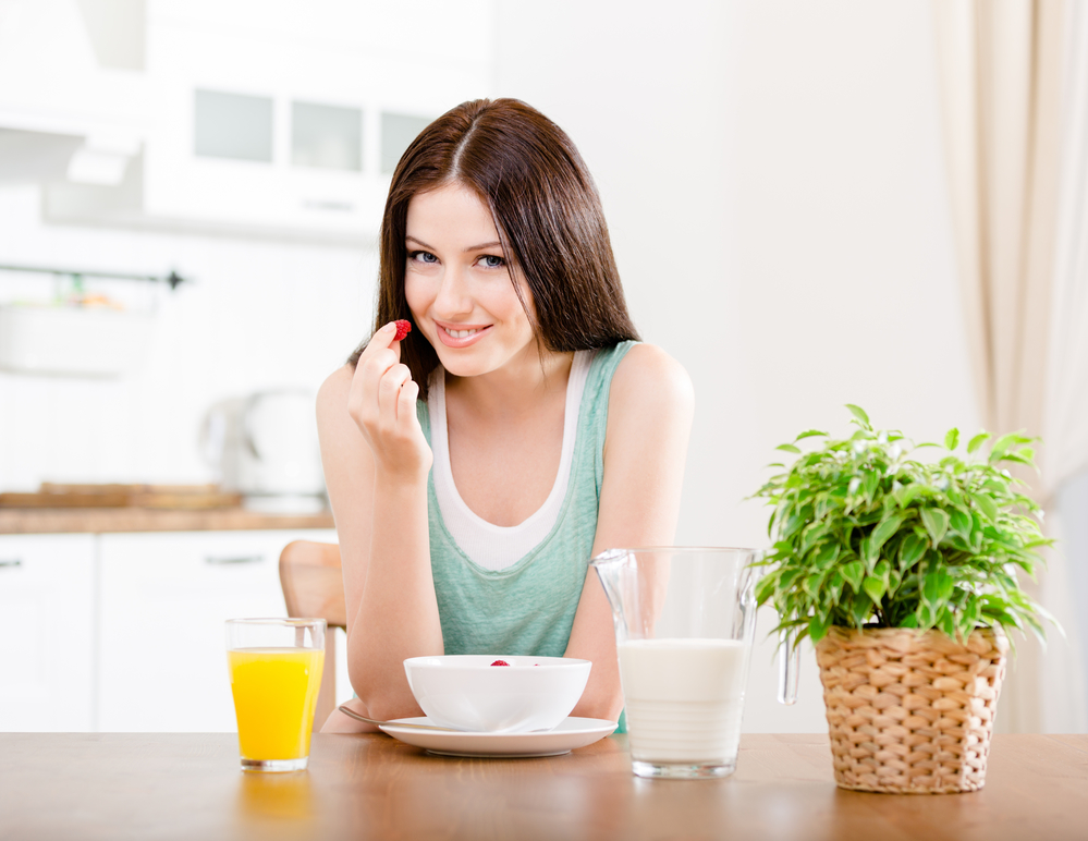 Portrait of the girl eating dieting cereals with milk and strawberry and orange juice sitting at the kitchen table