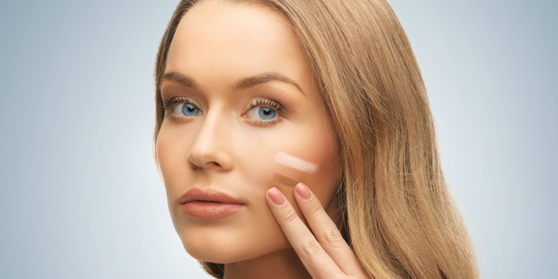 bright picture of beautiful woman applying foundation.